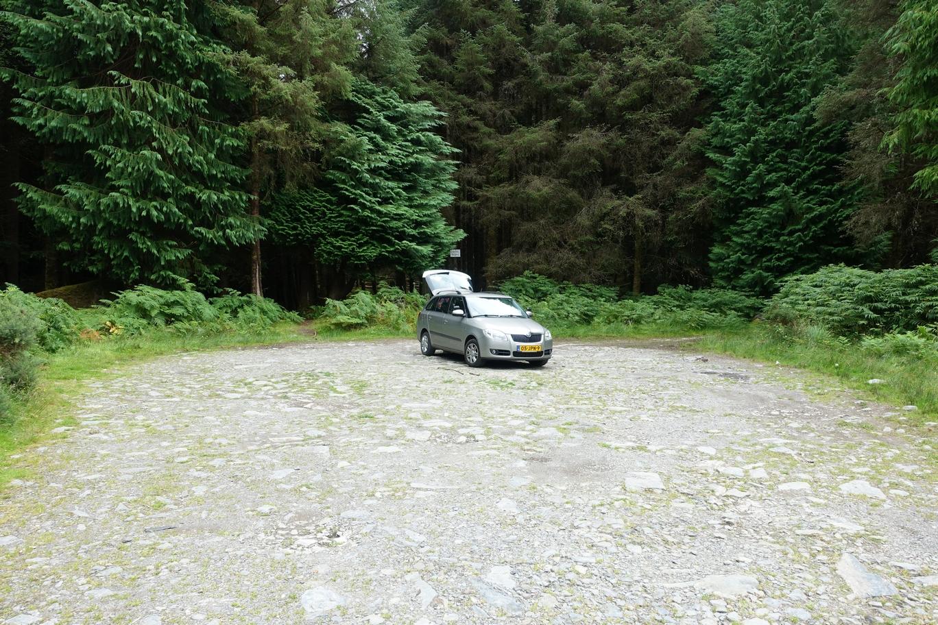 De auto op de parkeerplaats met daarachter toegang tot het bos